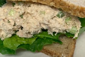 Albacore Tuna, Mayo, Seasonings, Celery, Greens on Oat Wheat Bread. Garnished with a Cherry Tomato and Pickles.